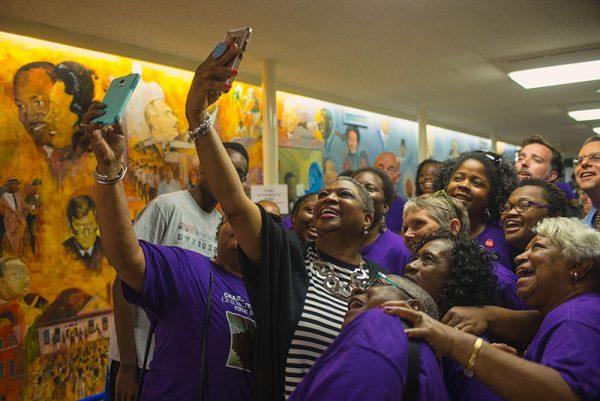 Women taking selfies in front of mural